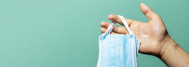 影付きのシアン、アクアメンテ色の背景にコロナウイルスを防ぐ医療インフルエンザマスクを持っている男性の手のクローズアップ。