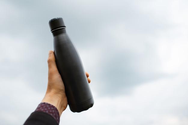 ぼやけた雲の背景に金属のボトルを持っている男性の手のクローズ アップ。