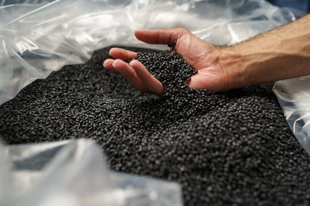 Крупным планом мужской руки, держащей гранулы пластикового полимера