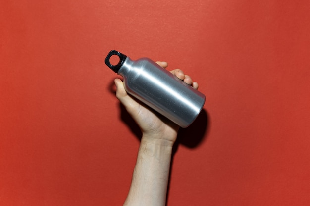 赤い色のスタジオの背景に、水用の再利用可能なアルミニウム魔法瓶を持っている男性の手のクローズアップ。ゼロウェイスト。プラスチックフリー。