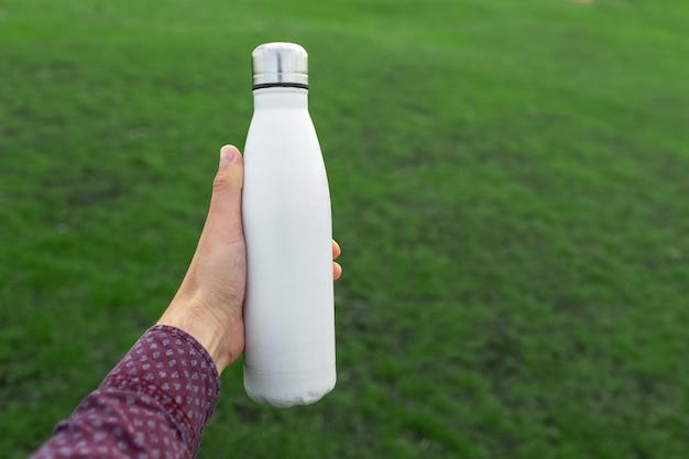 ぼやけた緑の草の背景に白い色の再利用可能なスチールサーモウォーターボトルを持っている男性の手のクローズアップ。