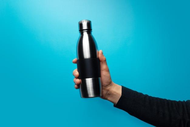 青い壁に再利用可能な鋼の水筒を持っている男性の手のクローズアップ。