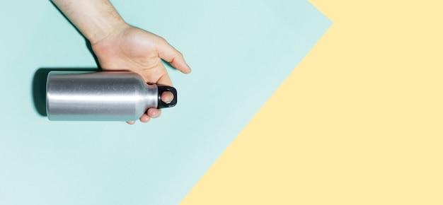 재사용 가능한 열 병을 들고 남성 손 클로즈업입니다. 파스텔 블루와 옐로우 색상의 배경입니다. 복사 공간 파노라마 사진.