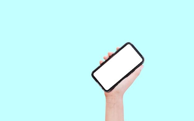 コピースペースとパステルブルーに分離された白いモックアップとスマートフォンを持っている男性の手のクローズアップ。
