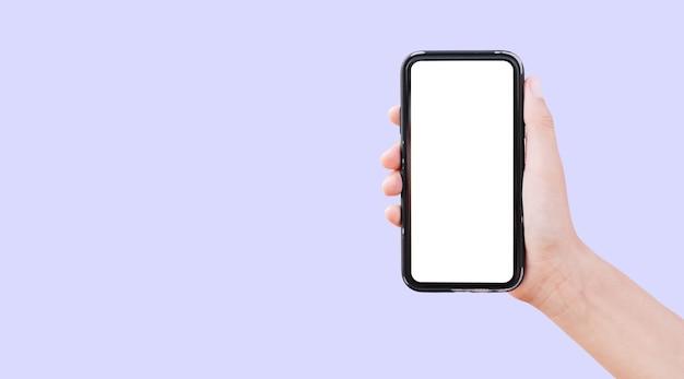 コピースペースとパステルパープルの背景に分離された白いモックアップとスマートフォンを持っている男性の手のクローズアップ。