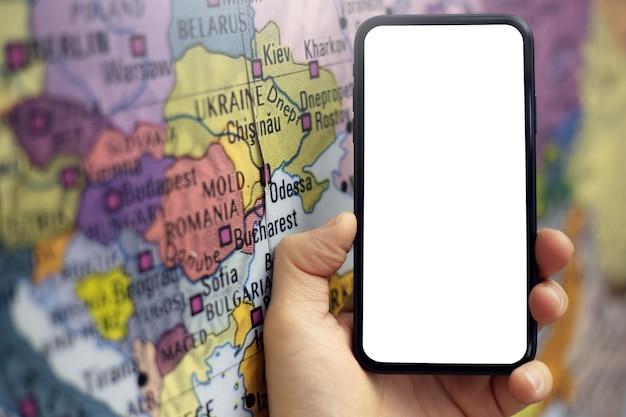 世界地図の近くに表示されている白いモックアップとスマートフォンを持っている男性の手のクローズアップ。