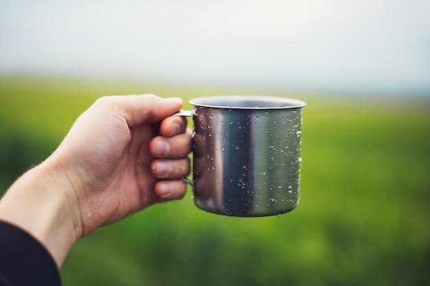 Крупный план мужской руки, держащей стальную чашку, опрысканную водой на фоне затуманенной зеленой травы.