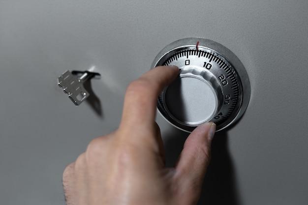 남성 손 클로즈업, 안전 잠금 장치의 조합 보안 코드를 소개합니다.