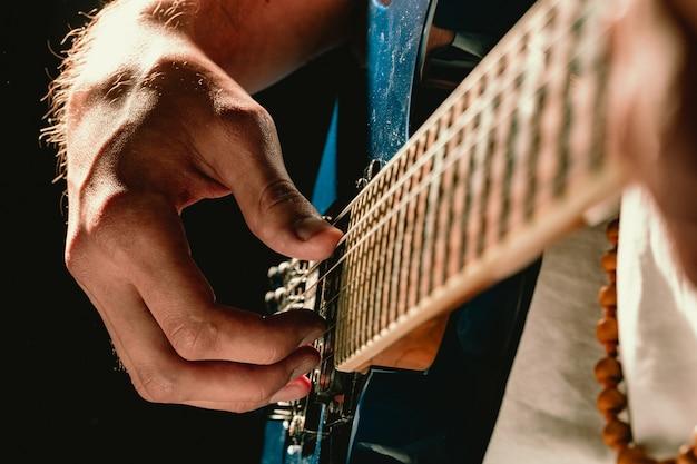 暗闇の中でエレクトリックギターを演奏する男性の手のクローズアップ
