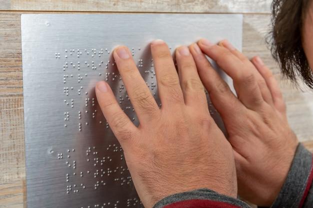 Крупным планом мужской руки, читающей текст брайля