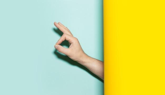 두 배경 노란색과 아쿠아 menthe 색상에 괜찮아 제스처를 보여주는 남성 손의 클로즈업.
