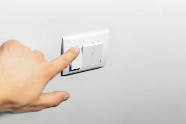 Крупный план мужской руки, включающей / выключающей свет кнопкой электрического переключателя