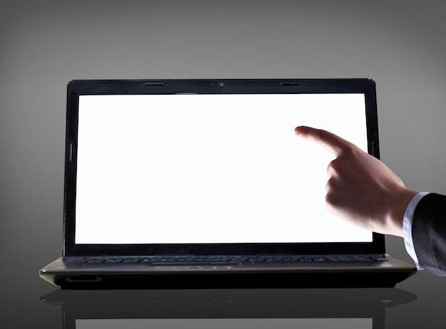 검정 배경 위에 노트북 화면에서 가리키는 집게 손가락으로 남성 손 클로즈업