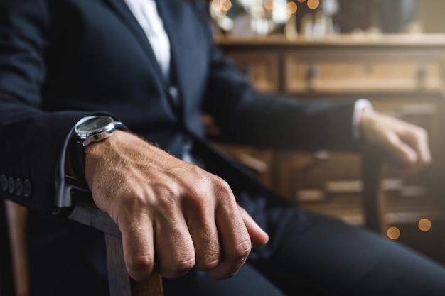 안락의 자에 손목 시계와 남성 손 클로즈업