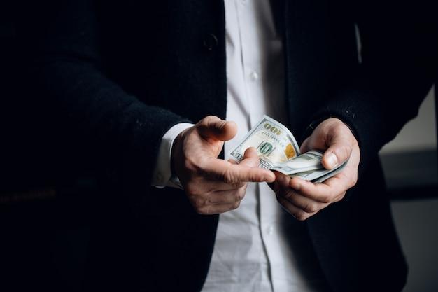 ドル札を数える男性の手のクローズアップ