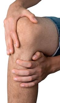 白で隔離の痛む膝を保持している男性の手のクローズアップ