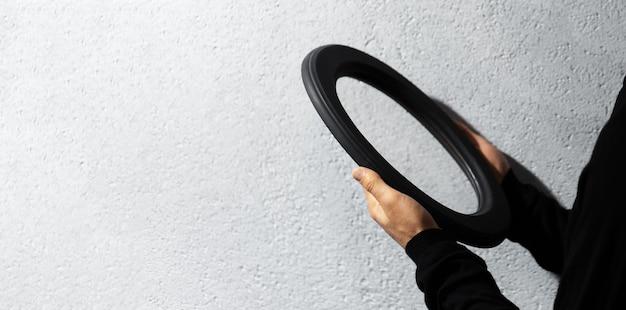 テクスチャードグレーの壁に黒い楕円形の鏡を保持している男性の手のクローズアップ