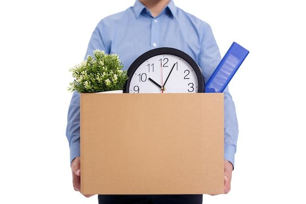 흰색 배경에 격리된 식물과 문서를 포함한 작업물이 있는 상자를 들고 있는 남성 손 클로즈업