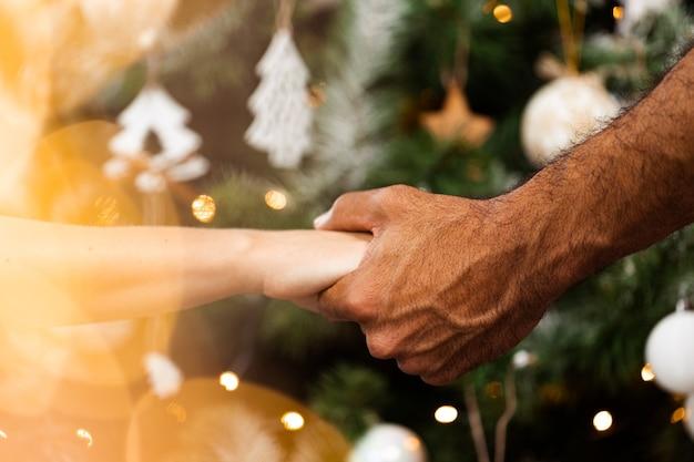 クリスマスのギフトボックスを保持している男性の手のクローズアップ
