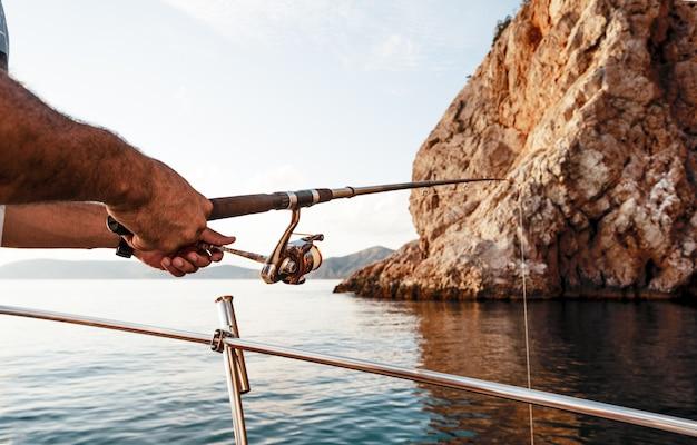 넓은 바다에서 요트에서 낚시를 하는 동안 낚싯대를 들고 있는 남성 손 클로즈업