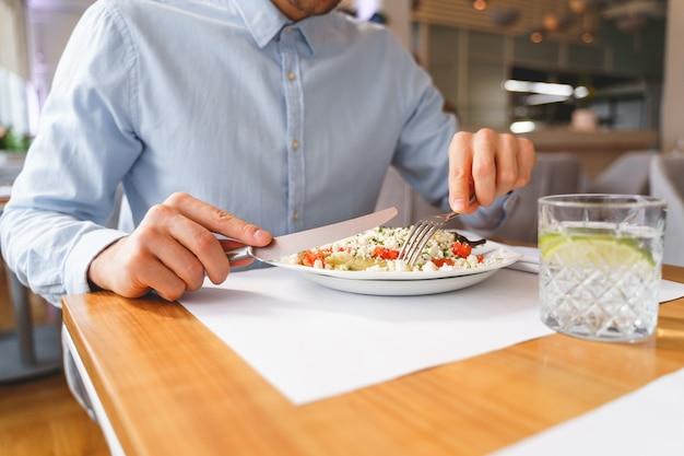 신사가 신선한 샐러드와 함께 테이블에 앉아 있는 동안 포크와 나이프를 들고 있는 남성 손 클로즈업