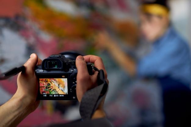 흐릿한 배경의 여성 예술가에게 전문 디지털 카메라를 들고 있는 남성 손 클로즈업