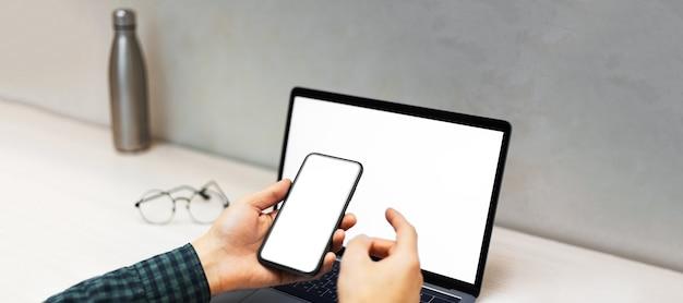 サーモウォーターボトルと丸い眼鏡とワークデスクの背景にモックアップとラップトップの横にスマートフォンを持っている男性の手のクローズアップ。