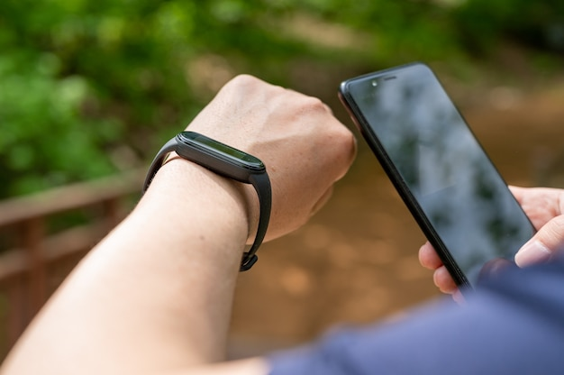 遊歩道でスマートウォッチとスマートフォンを保持している男性の手のクローズアップ