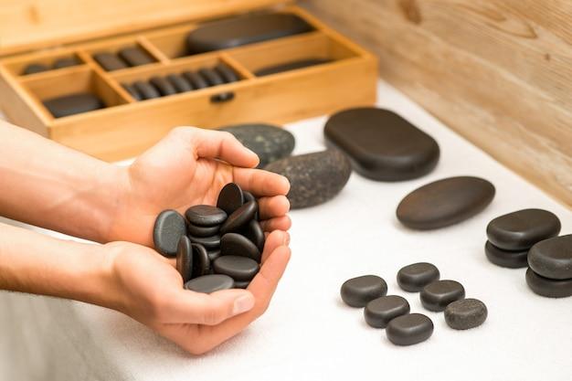 Крупным планом мужские руки, держащие черные камешки в ее ладонях над белым столом в спа-салоне