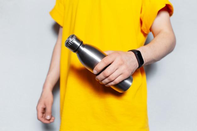 白い壁の背景に黄色のシャツを着て、鋼の再利用可能なサーモウォーターボトルを保持している男性の手のクローズアップ。