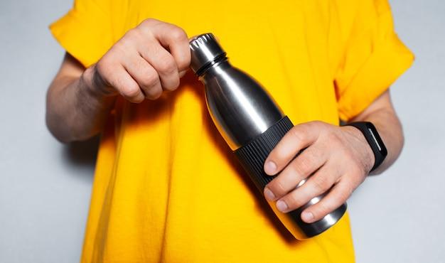 鋼の熱水ボトルを保持している男性の手のクローズアップ。