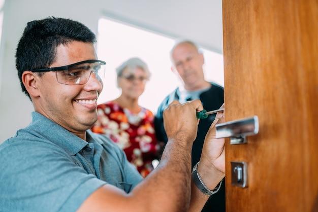 Крупным планом мужские руки ремонтируют или устанавливают металлический дверной замок. старшая пара в фоновом режиме.