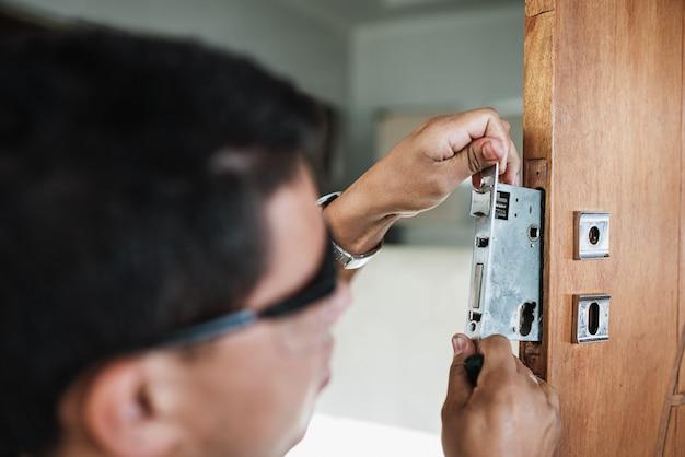 Крупным планом мужские руки ремонтируют или устанавливают металлический дверной замок.