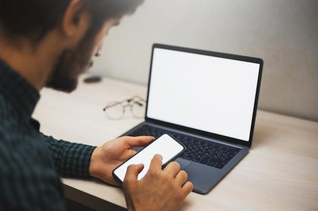 男性の手のクローズアップ、机の上のラップトップの壁にスマートフォンの画面に触れて、。
