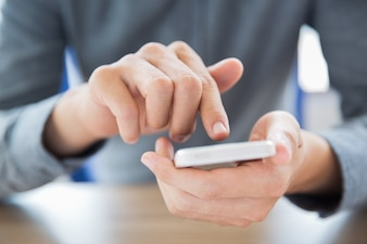 Close-up of male hands touching smartphone screen
