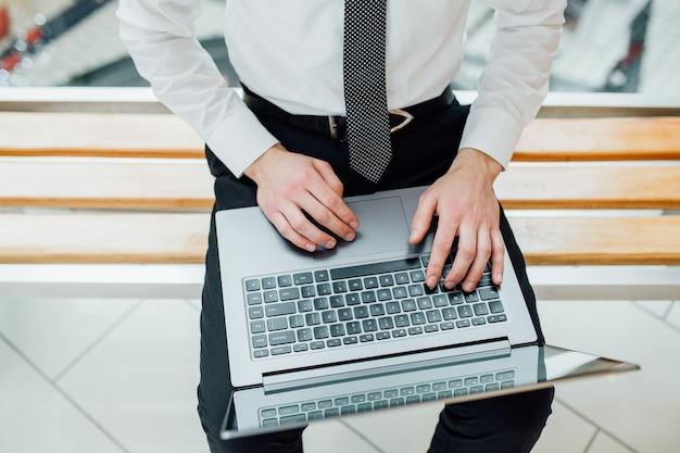 オフィスでラップトップを使用して男性の手のクローズアップ、インテリアでラップトップのキーボードで入力している男性の手、、コンピューターを使用してビジネスマンの側面図