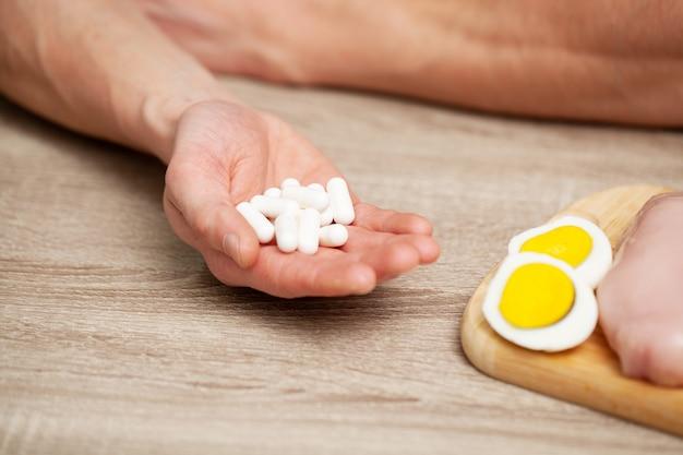 커팅 보드와 테이블에 알약에 단백질이 풍부한 음식으로 남성 손의 닫습니다
