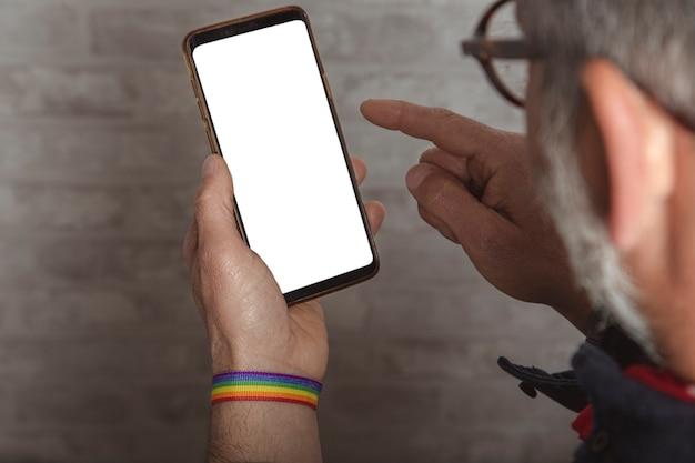 スマートフォンを使用してlgbtブレスレットと男性の手のクローズアップ