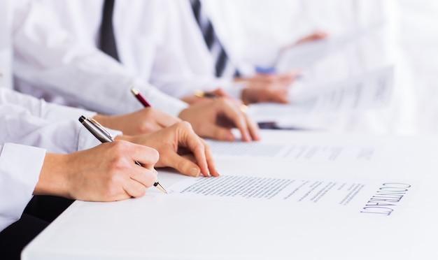 Крупный план мужских рук с ручкой над деловым документом Premium Фотографии