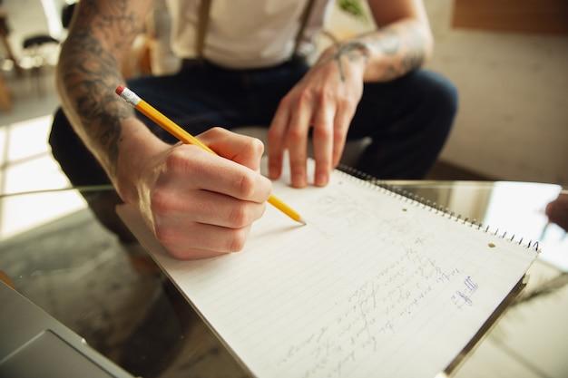 Закройте мужские руки, писать на пустой бумаге на столе у себя дома. делаем заметки, работаем на дому, отчитываемся за свою работу. образование, фриланс, искусство и бизнес-концепция. оставляет подпись, оформляет документы.
