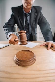 Крупный план судьи-мужчины, который дает вердикт, ударяя молотком на стол