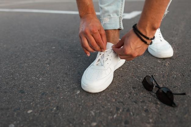 Крупный план мужских ног в синих винтажных джинсах в белых модных кожаных кроссовках. модный парень стоит на асфальте и поправляет шнурки на туфлях.