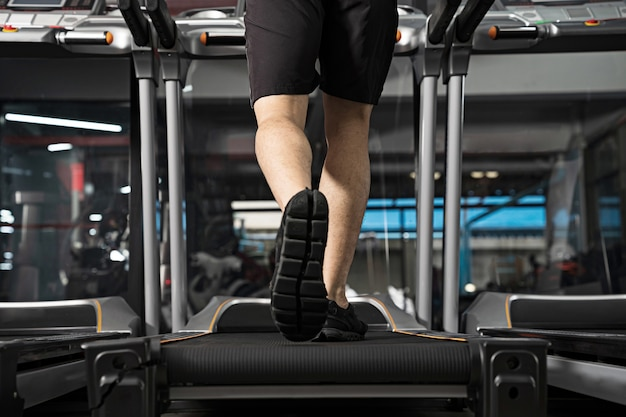 ジムでトレッドミルで実行されている男性の足のクローズアップ