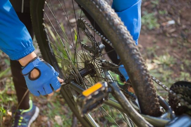 Крупным планом мужской горный байкер, исправление его велосипедной цепи