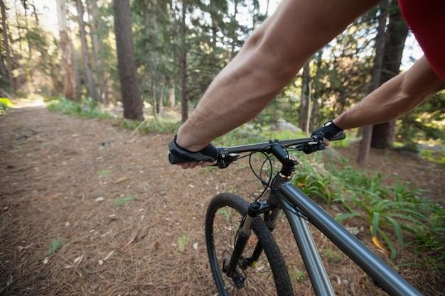 Крупным планом мужской горный байкер езда на велосипеде