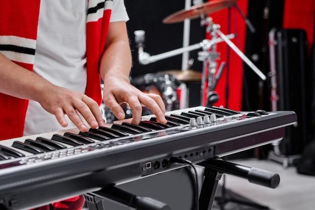 リハーサルベースの背景でシンセサイザーを演奏する男性ピアニストの指のクローズアップ