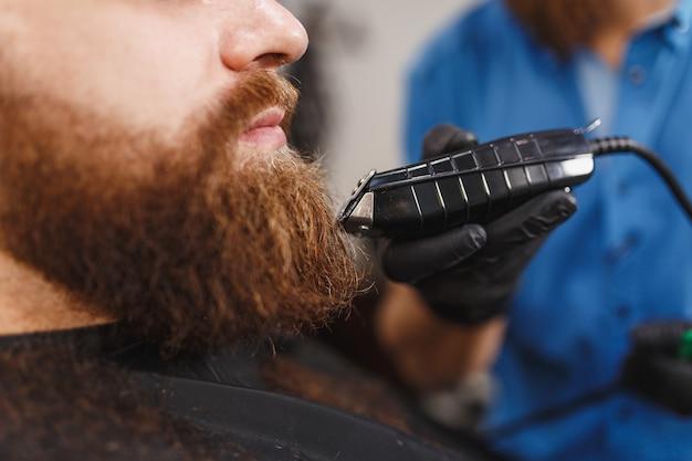 클리퍼로 두꺼운 큰 수염을 가진 클라이언트를 제공하는 남성 전문 미용사의 닫습니다