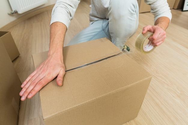접착 테이프를 가진 남성 씰링 골 판지 상자의 클로즈업