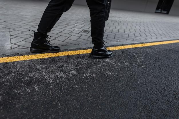 街のアスファルトに黒のトレンディなジーンズのトレンディな革のブーツで男性のスタイリッシュな脚のクローズアップ。ヴィンテージシューズの現代人が道を歩いています。男性のための新しい秋春の靴コレクション