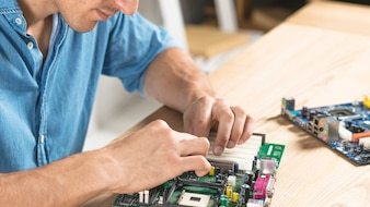 Close-up of male technician assembling motherboard